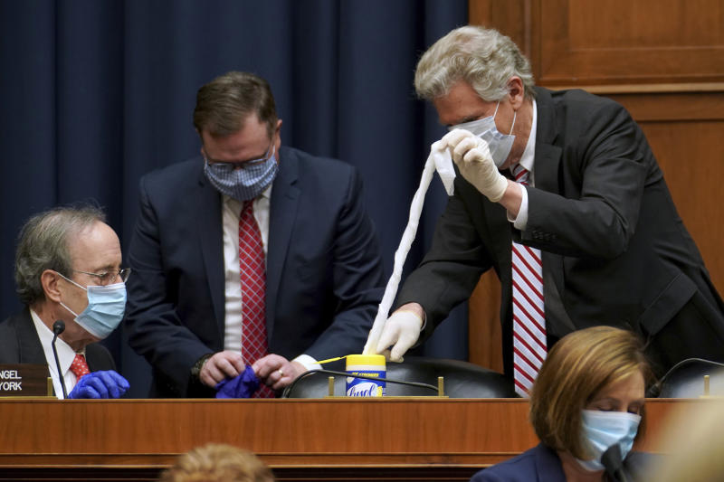 Rep. Eliot Engel, D-N.Y., and Rep. Frank Pallone, D-N.J., prepare to clean their seats before a House Energy and Commerce Subcommittee on Health hearing Thursday, May 14, 2020, on Capitol Hill in Washington. (Greg Nash/Pool via AP)