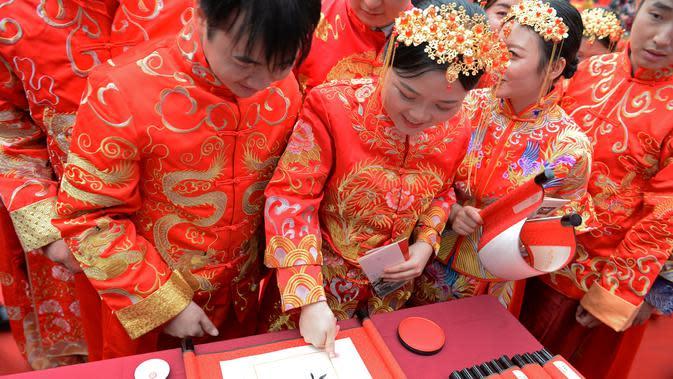 Mempelai membubuhkan sidik jari pada tulisan kaligrafi tradisional dalam pernikahan massal bergaya China di Changsha, Provinsi Hunan, China, 25 September 2020. Sebanyak 71 pasangan resmi menjadi suami-istri usai mengikuti upacara pernikahan tradisional dalam acara nikah massal. (Xinhua/Chen Zhenhai)
