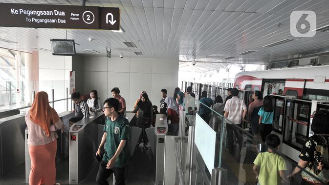 Kerumunan warga saat menggunakan jasa kereta LRT Jakarta di Stasiun Velodrome, Jakarta, Minggu (1/12/2019). Kereta LRT Jakarta rute Velodrome-Kelapa Gading beroperasi secara komersial mulai hari ini (1/12) dengan tarif Rp5.000 flat untuk sekali perjalanan. (merdeka.com/Iqbal S. Nugroho)