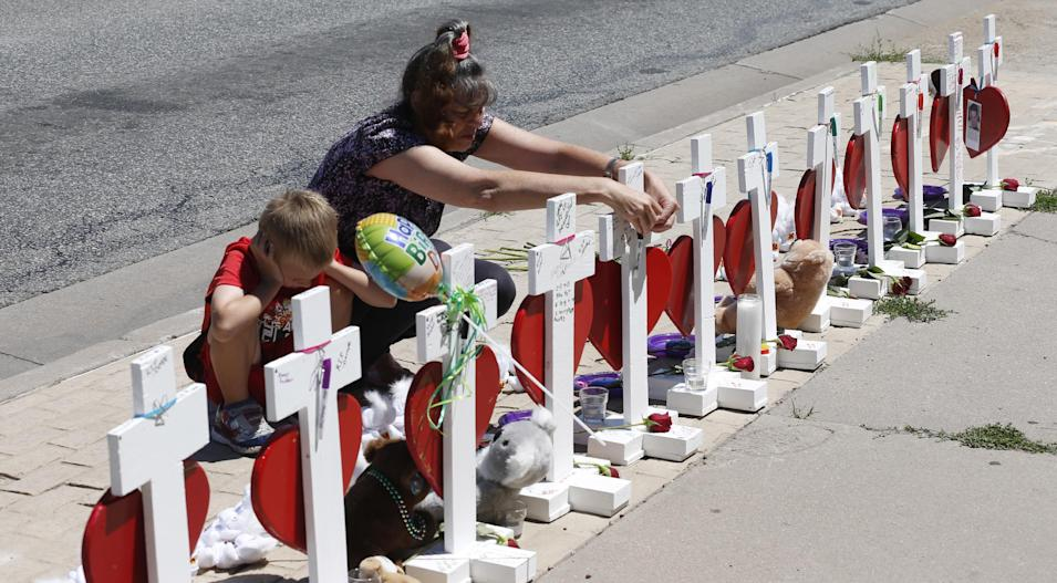 While her 6-year-old grandson, Ace, stays by her side, Kathi Darciprette, right, hangs a marker back on the cross for Micayla Medek, one of the victims of the massacre in a nearby movie theatre, after writing a message on a heart handing from the cross as mourners mark the day of the third anniversary of the shooting spree Monday, July 20, 2015, in Aurora, Colo. James Holmes, who had been working toward his Ph.D. in neuroscience, could get the death penalty for the massacre that left 12 people dead and dozens of others wounded early Friday, July 20, 2012. (AP Photo/David Zalubowski)