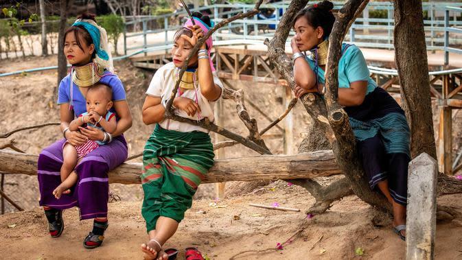 Perempuan Suku Kayan menunggu turis di luar kios suvenir mereka di Taman Chang Siam, Pattaya, Thailand, Rabu (12/2/2020). Chang Siam Park adalah salah satu primadona bagi wisatawan China di Pattaya yang kini berangsur sepi karena penyebaran virus corona covid-19. (Mladen ANTONOV / AFP)