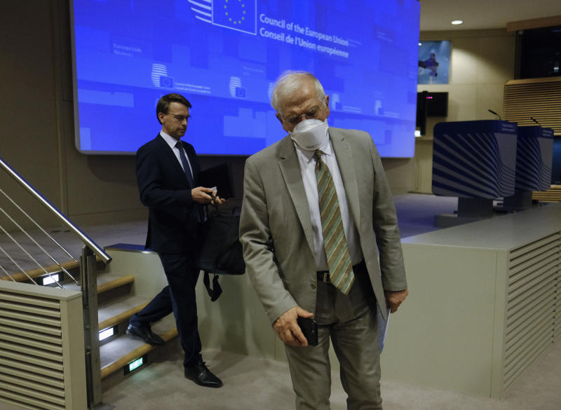 European Union foreign policy chief Josep Borrell, right, wears a mouth mask after addressing a video press conference at the conclusion of a video conference of EU foreign affairs ministers in Brussels, Wednesday, April 22, 2020. (Olivier Hoslet, Pool Photo via AP)