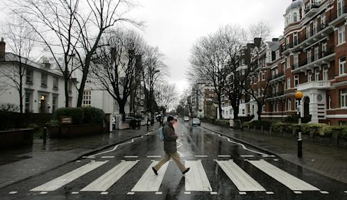 "FILE - In this file photo taken Feb. 16, 2010, a man walks on the zebra crossing made famous from the album cover of The Beatles' ""Abbey Road"" in front of Abbey Road Studios, seen at left, in London. London counts at least 11 Abbey Roads, with potential tourist pitfalls in neighborhoods such as Barking or Bexleyheath, both of which are on the outer edges of central London. In the British capital, as elsewhere, the common street name harkens back to the medieval priories that once dotted the area. (AP Photo/Akira Suemori, File)"