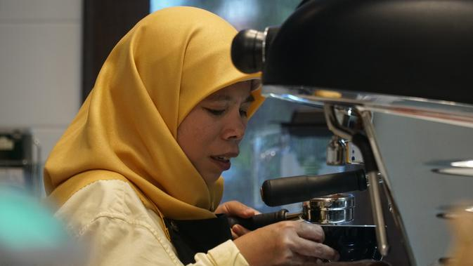 Barista Cafe More Pujianti (40) yang merupakan penyandang disabilitas sensorik sedang menyiapkan kopi untuk diseduh. (Liputan6.com/Huyogo Simbolon)