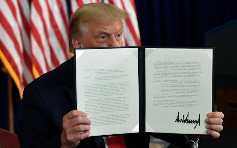 Donald Trump signed an executive order during a news conference at the Trump National Golf Club - AP