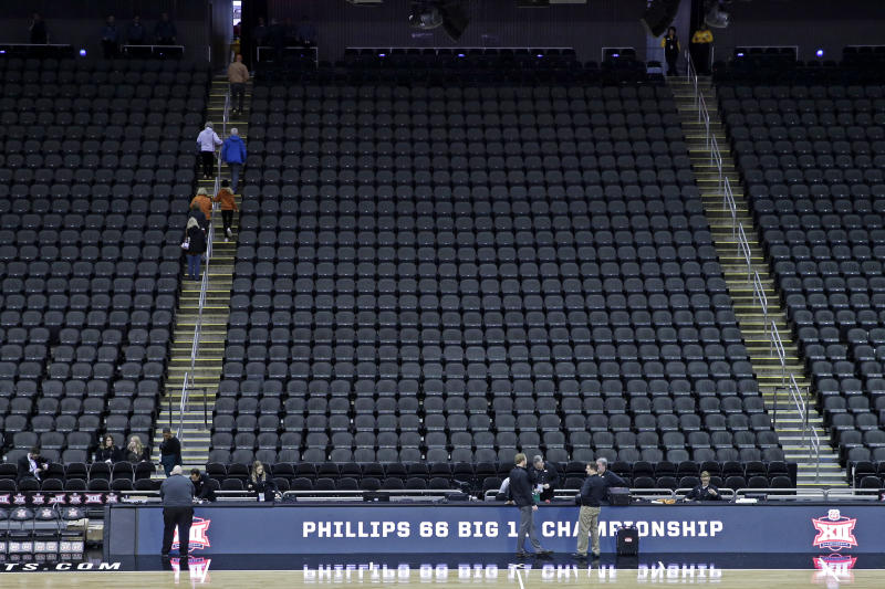 Fans leave the Sprint Center after the remaining NCAA college basketball games after in the Big 12 Conference tournament were canceled due to concerns about the coronavirus Thursday, March 12, 2020, in Kansas City, Mo. (AP Photo/Charlie Riedel)
