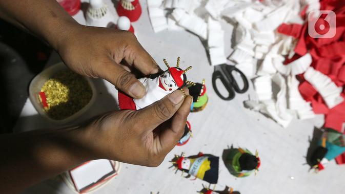 Pekerja membuat ondel-ondel dari shuttlecock atau kok bekas di perkampungan Budaya Betawi, Srengseng Sawah, Jakarta, Sabtu (8/8/2020). Menyambut HUT Kemerdekaan RI, pesanan ondel-ondel dari shuttlecock bekas dengan harga Rp 5 ribu per buahnya mulai banyak diburu. (Liputan6.com/Fery Pradolo)
