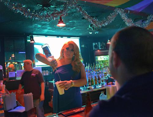 "This Saturday, Dec. 21, 2013 photo shows Jordan Williams, who goes by the stage name Tanzi Taylor, mixing a drink at Club Pink, a bar for Lesbian Gay Bisexual and Transexual customers owned by Tommy Stewart, left, in Monroe, La. Monroe neighbors West Monroe, the hometown of Phil Robertson, the patriarch from the popular ""Duck Dynasty"" series. Robertson was suspended last week for disparaging comments he made to GQ magazine about gay people. (AP Photo/Matthew Hinton)"
