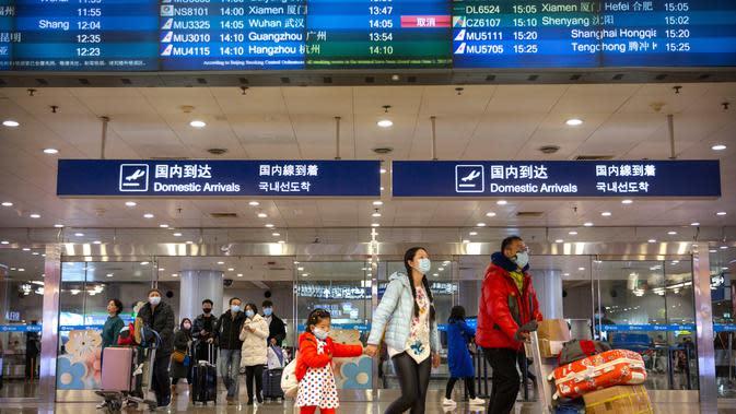 Penerbangan dari Wuhan Ditutup: Pelancong berjalan melintasi papan informasi tentang penerbangan dari Wuhan telah dibatalkan di Bandara Internasional Ibu Kota Beijing pada Kamis (23/1/2020). China menangguhkan semua transportasi dari dan ke kota pusat penyebaran virus corona. (AP/Mark Schiefelbein)