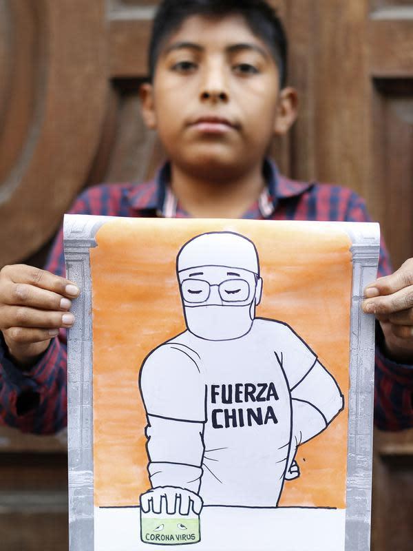 Jose Hernandez, seorang bocah lelaki Meksiko berusia 11 tahun, memperlihatkan gambar hasil karyanya untuk mendukung perjuangan China melawan coronavirus baru di Mexico City, Meksiko, (7/2/2020). (Xinhua/Francisco Canedo)