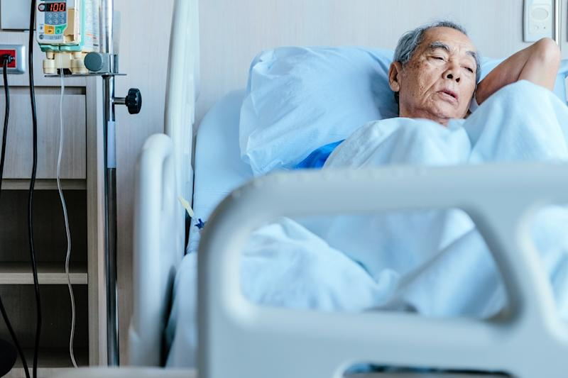 Older Asian Man Lying in a Hospital Bed, over 50 regrets