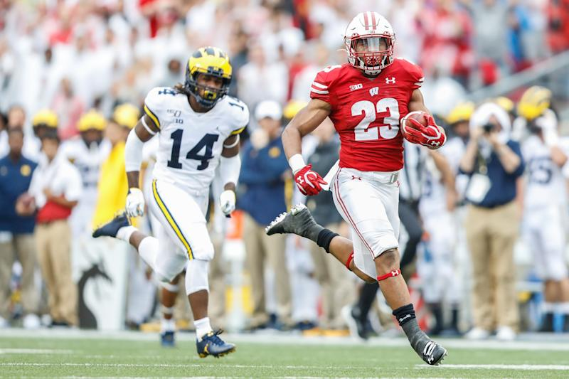 Wisconsin running back Jonathan Taylor (23) runs away from Michigan defensive back Josh Metellus (14) to score a touchdown during the Badgers' win on Saturday. (Getty)