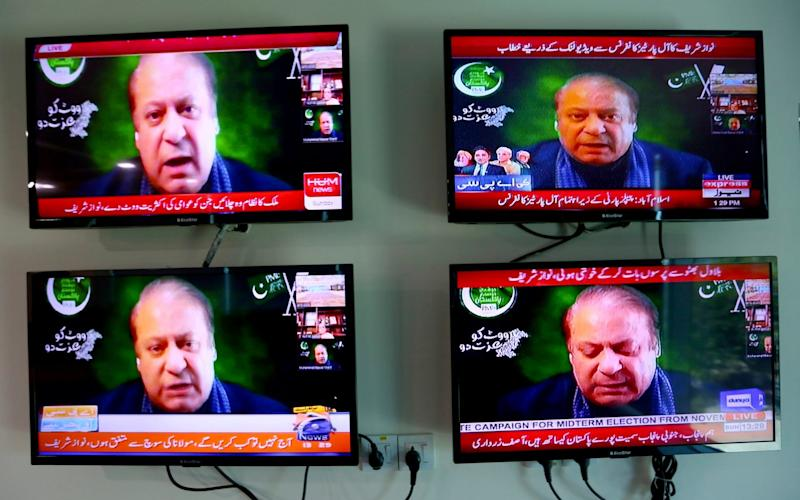 Pakistani news channels telecast live of Pakistan's ailing former Prime Minister Nawaz Sharif addressing to an opposition parties meeting in Islamabad, Pakistan on Sunday, Sept. 21, 2020. Sharif broke a yearlong silence from exile in London to vow to oust Imran Khan from office, accusing him of only reaching power through a vote rigged by the country's powerful military. (AP Photo/Anjum Naveed)