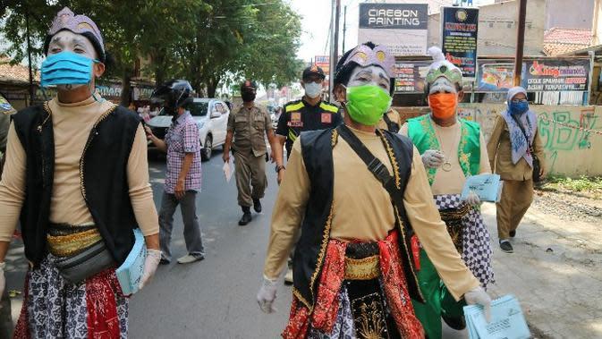 Tiga tokoh pewayangan turun sosialisasi kepada pedagang agar turut serta patuh terhadap aturan PSBB di Kota Cirebon dengan menutup tokonya. Foto (Liputan6.com / Panji Prayitno)