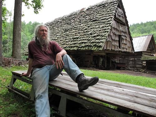 Eustace Conway rests on a wooden sledge in front of the horse barn at his Turtle Island Preserve in Triplett, N.C., on Thursday, June 27, 2013. People come from all over the world to learn natural living and how to go off-grid, but local officials ordered the place closed over health and safety concerns. (AP Photo/Allen Breed)