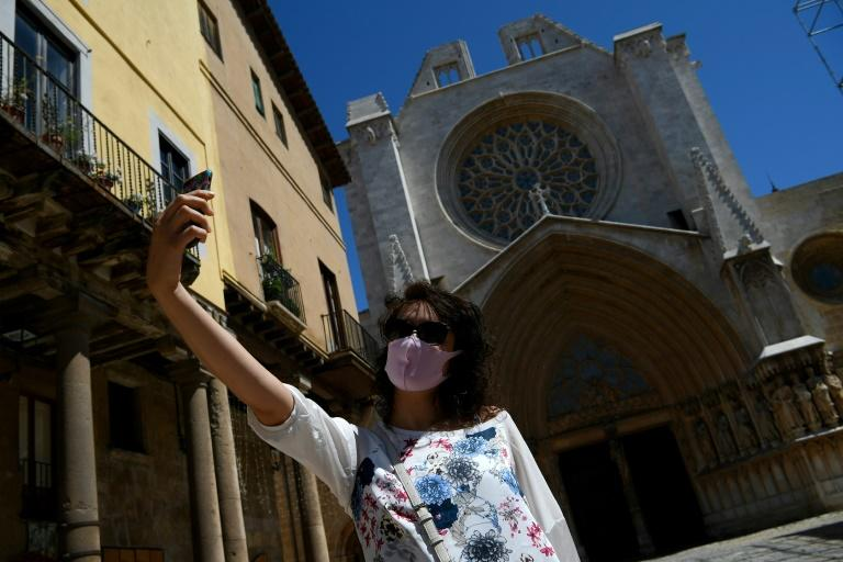 Venturing out, but with a mask, a woman takes a selfie outside Tarragona Cathedral as Spain, one of the countries worst hit by the coronavirus, looks to move gingerly back towards normal