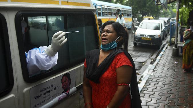 Seorang petugas kesehatan yang mengenakan alat pelindung diri (APD) mengambil sampel swab seorang wanita untuk menguji virus corona Covid-19, dari ambulans di depan pasar kota, di Kolkata (1/9/2020). (AFP/Dibyangshu Sarkar)