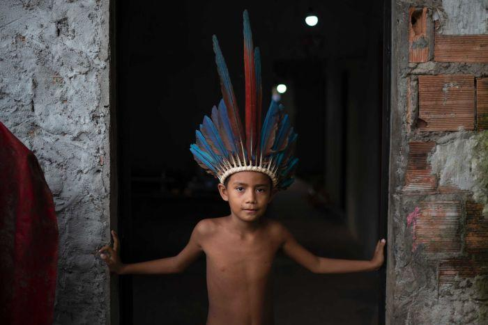 A little indigenous Brazilian boy in a feather head dress looks strong while standing in a doorway