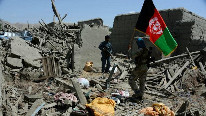 Seorang tentara nasional Afghanistan memegang bendera resmi negara tersebut (AFP Photo)