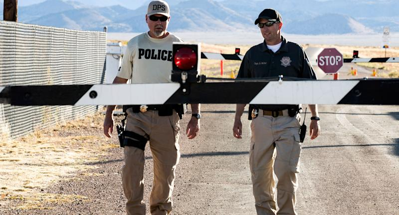 Police walk down gravel road at Area 51 site amid a scheduled raid in the Nevada desert.
