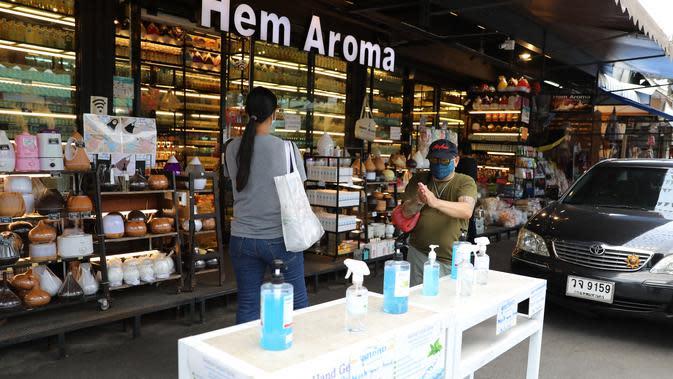 Pelanggan membersihkan tangan dengan cairan disinfektan saat berbelanja di Pasar Akhir Pekan Chatuchak di Bangkok, 9 Mei 2020. Pasar akhir pekan terbesar di Thailand ini kembali dibuka untuk hari pertama pada Sabtu (9/5) dengan sejumlah langkah ketat demi mengatasi COVID-19. (Xinhua/Zhang Keren)