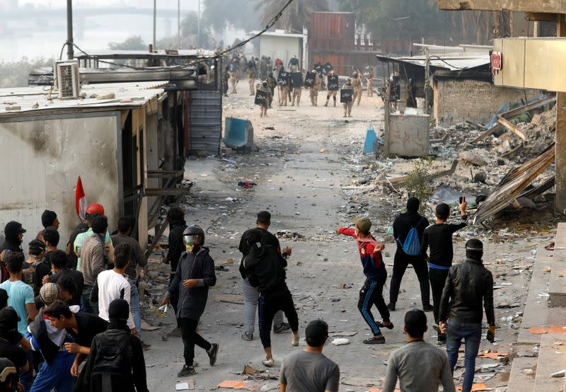 FILE PHOTO: Iraqi demonstrators throw stones towards Iraqi security forces during the ongoing anti-government protests, in Baghdad