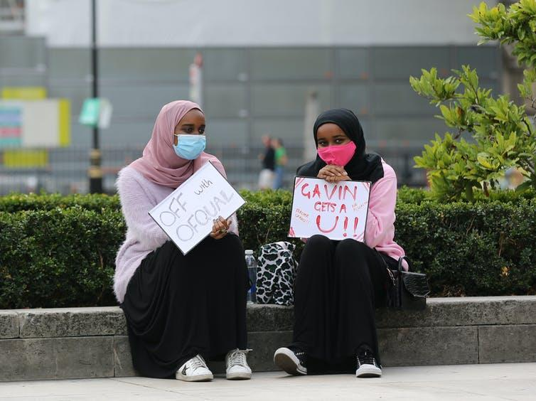 Two young female protesters sit with signs targeting Ofqual and Gavin Williamson.