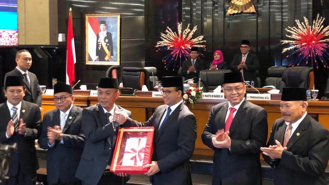 Ketua DPRD DKI Prasetyo Edi Marsudi bersalaman dengan Gubernur DKI Anies Baswedan usai pengesahan APBd-P 2019. (Delvira Hutabarat/Liputan6.com)