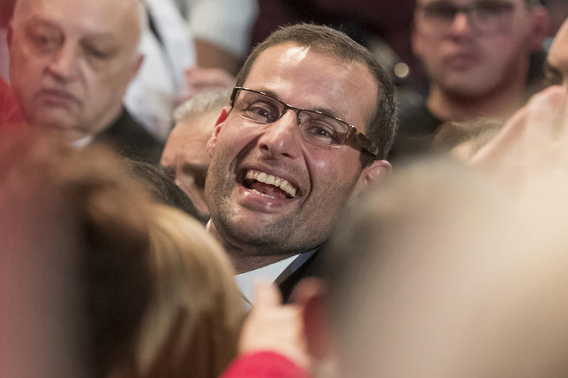 Robert Abela, who will be sworn in as Prime Minister of Malta Monday, is congratulated by a large crowds of supporters inside a volleyball court in Kordin, Malta, Sunday, Jan. 12, 2020. A first-term lawmaker whose father was Malta's president, Abela has been chosen to be the country's prime minister, replacing Joseph Muscat after weeks of protests demanding accountability in the investigation of the car bomb slaying of an anti-corruption journalist who targeted his government. (AP Photo/Rene' Rossignaud)