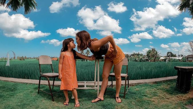 Gempi dan Gisel terlihat berada di persawahan nan hijau. Pemandangannya pun begitu indah. Gempi cantik dengan dress oranye, dan Gisel mengenakan hot pants dan tank top. Keduanya saling menatap berdekatan. (Instagram/gisel_la)