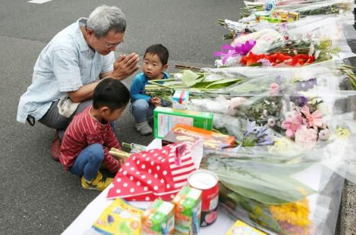 Residents pray at an altar for a nine-year-old student killed in Monday's earthquake in Osaka