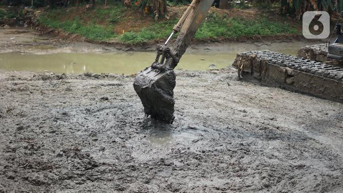 Petugas Sudin Sumber Daya Air (SDA) menggunakan alat berat untuk mengeruk lumpur yang mengendap di Setu Mangga Bolong, Jagakarsa, Jakarta, Rabu (2/9/2020). Pengerukan untuk meningkatkan fungsi setu sebagai tangkapan air, pengendali banjir dan penambahan daya tampung. (Liputan6.com/Immanuel Antonius)