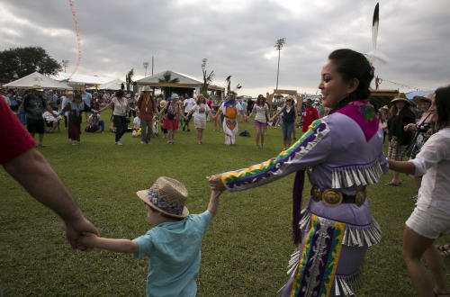 In this Friday, April 26, 2013 photo, the Yellow Bird Indian Dancers lead a dance at the Cultural Exchange Pavilion celebrating Native America culture during the New Orleans Jazz and Heritage Festival, in New Orleans. Louisiana Native Americans have long been represented at Jazz Fest, but this is the first year the focus on the culture has been expanded to include tribal nations from elsewhere in the United States, as well as Canada and Latin America. (AP Photo/Doug Parker)