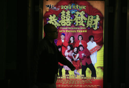 "In this Wednesday Feb. 13, 2013 photo, a man walks past the advertisement of a Hong Kong movie "" I Love Hong Kong 2013 "" in Hong Kong. Tens of millions of film fanatics are entering theaters around Asia during the long Lunar New Year holiday. This year's Hong Kong holiday crop includes ""Journey to the West: Conquering the Demons,"" a prequel to the classic Chinese fable, and ""I Love Hong Kong 2013,"" a super-light comedy with an all-star cast and a crowd-pleasing happy ending. Explaining her preference for watching locally-produced comedies, Hong Kong movie-goer Christine Lam said it reinforced the spirit of the season. (AP Photo/Vincent Yu)"