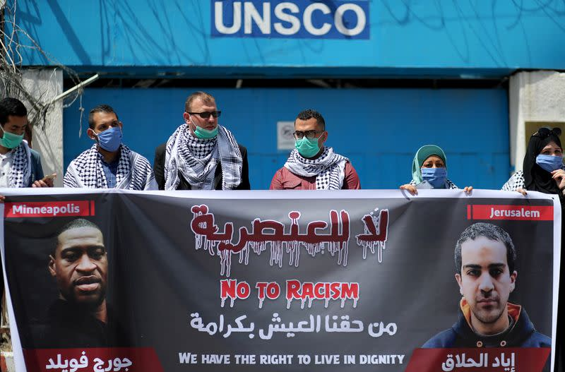 Palestinians hold a banner with pictures of George Floyd and and Iyad al-Halaq, during a protest against racial inequality, in Gaza City
