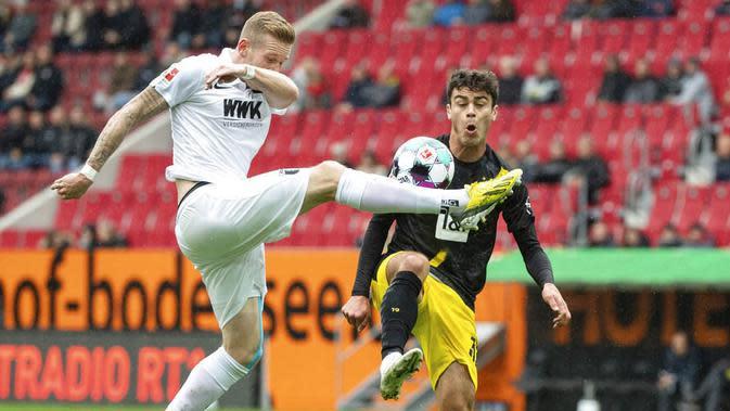 Pemain Borussia Dortmund, Giovanni Reyna, berebut bola dengan pemain Augsburg, Andre Hahn, pada laga Bundesliga, Minggu (27/9/2020). Augsburg menang dengan skor 2-0. (Matthias Balk/dpa via AP)