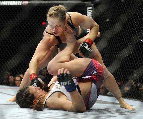 Ronda Rousey of Venice, Calif., punches Miesha Tate of Yakima, Wash., during the UFC 168 mixed martial arts women's bantamweight title fight on Saturday, Dec. 28, 2013, in Las Vegas. Rousey won by a third round tap out. (AP Photo/David Becker)