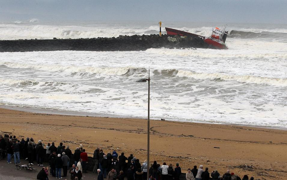 "People watch as waves knock against the wreck of the Spanish cargo ship ""Luno"" that slammed into a jetty in choppy Atlantic Ocean waters and broke in two, off Anglet, southwestern France, Wednesday, Feb. 5, 2014. The ship had been heading to a nearby port to load up with cargo when its engine failed and the rough waves carried it into the jetty. (AP Photo/Bob Edme)"
