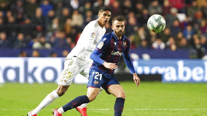Bek Real Madrid, Raphael Varane, mengawal pemain Levante, Borja Mayoral, pada laga La Liga di Stadion Ciutat de Valencia, Sabtu (22/2/2020). Levante menang 1-0 atas Real Madrid. (AP/Alberto Saiz)