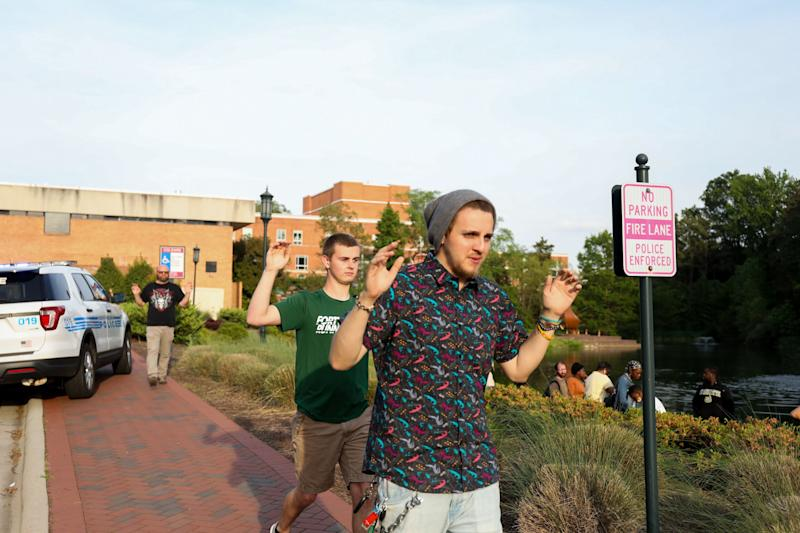 University students are seen leaving campus with their hands up. Source GettyMore