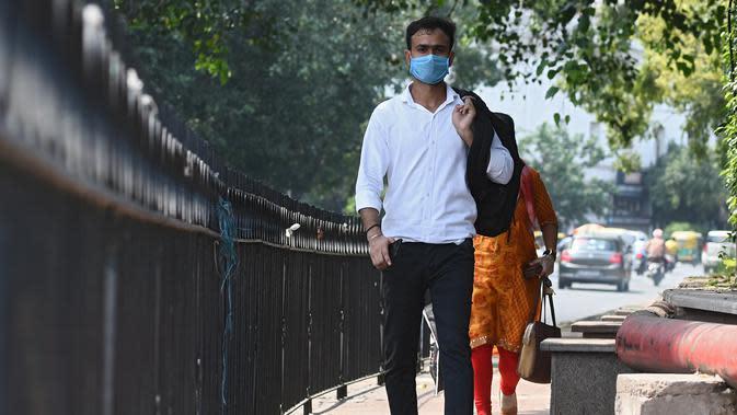 Seorang pria mengenakan masker berjalan di sepanjang jalan di New Delhi (16/9/2020). Total kasus Covid-19 di India melampaui lima juta pada 16 September, data kementerian kesehatan menunjukkan Pandemi meluas cengkeramannya di negara tersebut. (AFP/Sajjad Hussan)