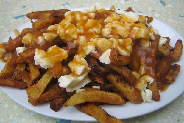 "This may be a Quebec specialty but poutine is a who affectionately refer to it as ""a heart-attack in a bowl."" It's really a huge plate of French fries smothered in cheese curds (the solid parts of curdled milk) and drowned in steaming hot gravy. Sometimes some extra cheese is melted over the top (depending, probably, on how much comfort you really need). Not only is it warm and heartening, but some late-night revelers also claim it can magically prevent hangovers."