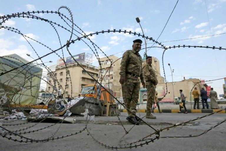 Iraqi policemen stand behind barbered wire during anti-government demonstrations in Baghdad's Tahrir Square on March 1, 2020