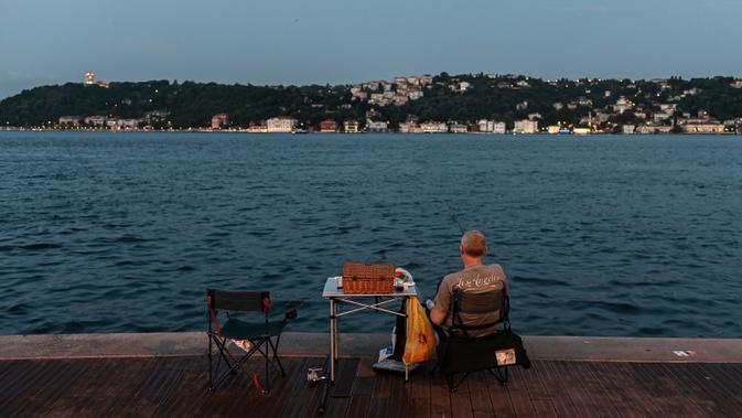Orang-orang menikmati malam di sebelah pantai Bosphorus ketika jembatan Fatih Sultan Mehmet terlihat di Istanbul (6/7/2020). Ketika diselesaikan pada 1988, jembatan tersebut menjadi jembatan gantung terpanjang ke-5 di dunia; sekarang jembatan tersebut berada pada urutan ke-19. (AFP/Ozan Kose)