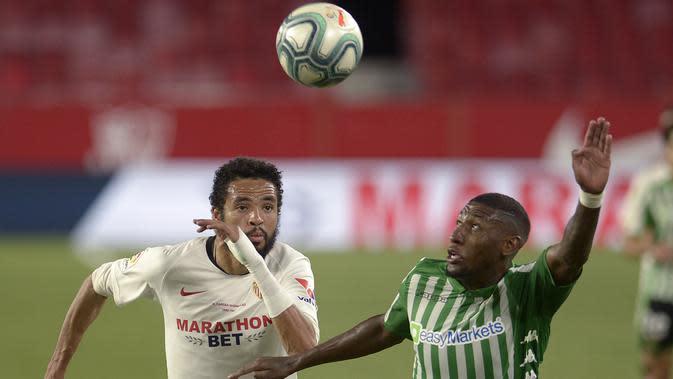 Penyerang Sevilla, Youssef En-Nesyri, berebut bola dengan bek Real Betis, Emerson Aparecido, pada laga lanjutan La Liga di Estadio Ramon Sanchez Pizjuan, Jumat (12/6/2020) dini hari WIB. Sevilla menang 2-0 atas Real Betis. (AFP/Cristina Quicler)