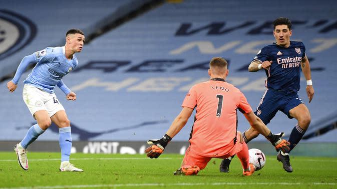 Penjaga gawang Arsenal Bernd Leno (tengah) melakukan penyelamatan di depan pemain Manchester City Phil Foden (kiri) pada pertandingan Liga Premier Inggris di Etihad Stadium, Manchester, Inggris, Sabtu (17/10/2020). Manchester City menang 1-0. (Michael Regan/Pool via AP)