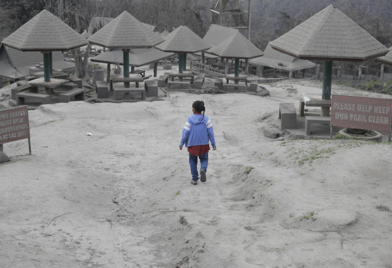 """A woman walks along a park covered in volcanic-ash at a town near Taal volcano in Tagaytay, Cavite province, southern Philippines on Sunday Jan. 19, 2020. Philippine officials said Sunday the government will no longer allow villagers to return to a crater-studded island where an erupting Taal volcano lies, warning that living there would be """"like having a gun pointed at you."""" (AP Photo/Aaron Favila)"""