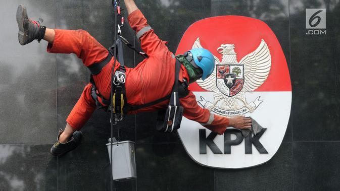 Pekerja membersihkan debu yang menempel pada tembok dan logo KPK di Gedung KPK, Jakarta, Rabu (21/11). KPK merilis Indeks Penilaian Integritas 2017. (Merdeka.com/Dwi Narwoko)