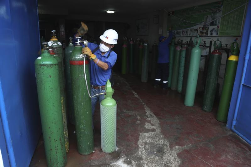 A worker wearing a mask to prevent the spread of the new coronavirus refills an empty oxygen cylinder in Callao, Peru, Wednesday 3, 2020. Long neglected hospitals in Peru and other parts of Latin America are reporting shortages of Oxygen as they confront the COVID-19 pandemic. (AP Photo/Martin Mejia)