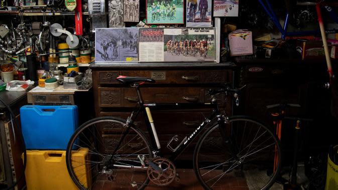 Sebuah gambar menunjukkan Raffaello Bianco, mekanik dan pecinta sepeda di bengkel mekaniknya di ruang bawah tanah apartemennya di Turin, Italia, 7 Juli 2020. Raffaello Bianco adalah montir sepeda amatir yang sedang memperbaiki sepeda di garasi kecil dekat rumahnya. (MARCO BERTORELLO/AFP)